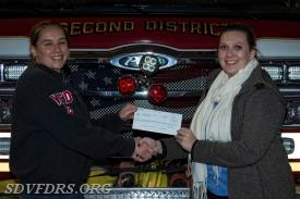 Fire Lieutenant/Fire Prevention Officer Heather Bean accepts the US$2,594 check from FM Global engineer Ms. Dallas Gage.